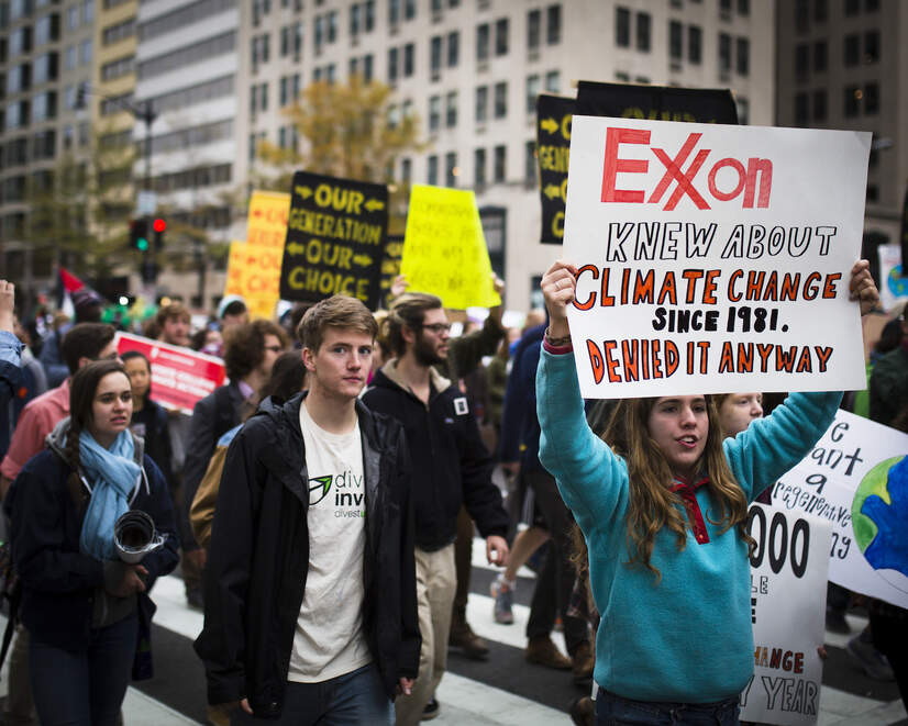 Protesters with signs saying 'Exxon knew about climate change since 1981. Denied it anyway.'