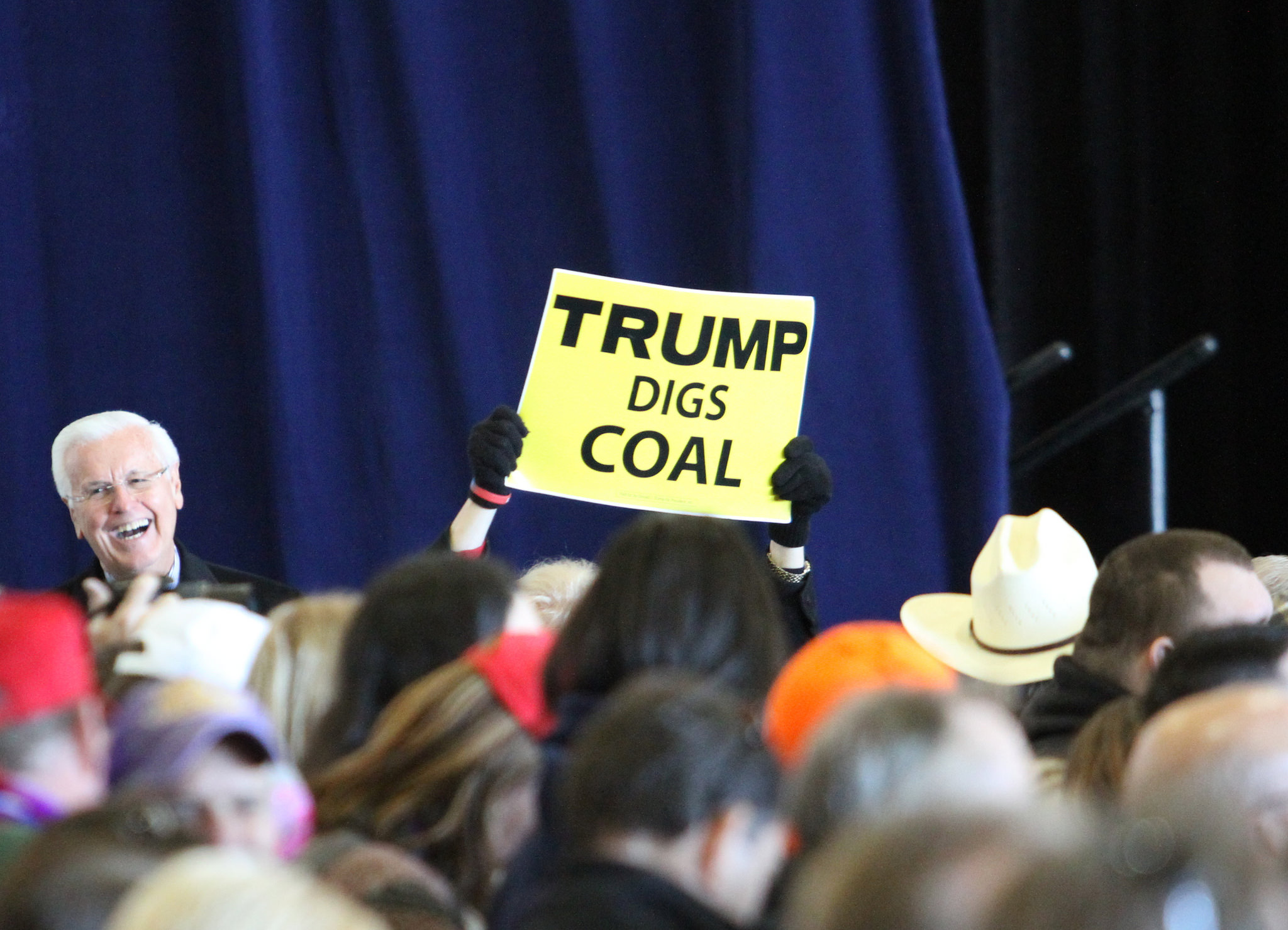 Someone holding a 'Trump digs coal' sign at a rally